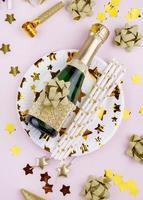 Champagner und Dekorationen auf rosa Hintergrund foto