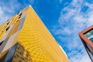 kontrastierende Farben und Formen auf Gebäudefassaden gegen den Himmel in Manchester, Großbritannien foto