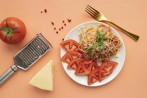 Nudeln mit Tomaten auf orangefarbenem Hintergrund foto