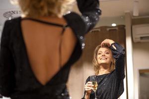 attraktive Frau, die am Spiegel trinkt foto