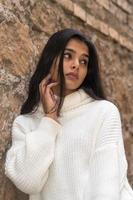 nachdenkliche und kontemplative brünette Frau, die einen Rollkragenpullover oder einen Pullover trägt, der zur Seite schaut foto