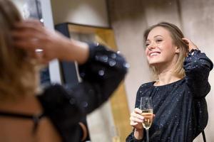 attraktive junge Frau, die am Spiegel trinkt foto