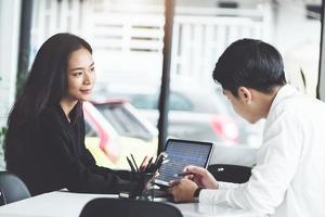 Zwei Geschäftsleute diskutieren Diagramme auf dem Tablet foto