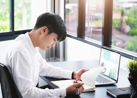 Geschäftsmann, der Notizbuch mit Laptop betrachtet foto