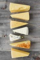dreieckiges Käsestück arrangierte Reihe Holzbrett. schöne Qualität und Auflösung schönes Fotokonzept foto