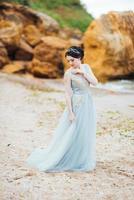 Braut in einem Blaulichtkleid, das entlang des Ozeans geht foto