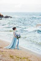 Braut mit einem Blumenstrauß am Strand foto