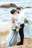 das gleiche Paar mit einer Braut in einem blauen Kleid zu Fuß foto