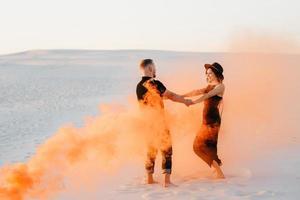 Mann und ein Mädchen in schwarzer Kleidung umarmen sich und rennen auf dem weißen Sand foto