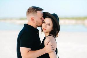 junges Paar ein Mann mit einem Mädchen in schwarzen Kleidern geht auf dem weißen Sand foto