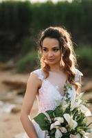 Braut mit einem Hochzeitsstrauß am Ufermeer foto