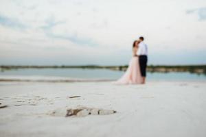 Ein junges Paar, ein Mann in einer schwarzen Reithose und ein Mädchen in einem rosa Kleid, gehen den weißen Sand entlang foto