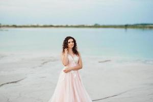 Mädchen in einem rosa Kleid gehen entlang des weißen Sandes foto