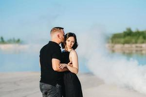 Mann und ein Mädchen in schwarzer Kleidung umarmen sich in einem Rauch foto