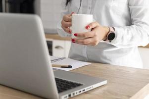 Person, die am Schreibtisch Kaffee trinkt foto