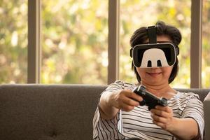 Ältere asiatische Frau, die ein Virtual-Reality-Brillensystem im natürlichen Wohnzimmerhintergrund mit moderner Technologie verwendet foto