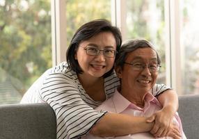 Senior asiatischer Mann und Frau entspannen im Urlaub im natürlichen Wohnzimmerhintergrund mit moderner Technologie foto
