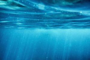 Oberflächenwelligkeit unter Wasser blauen Ozean mit Sonnenstrahl im tropischen Meer foto