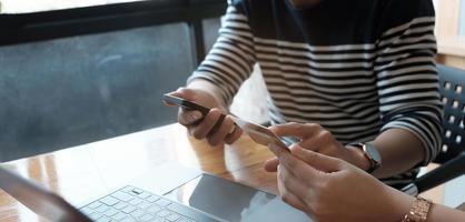 Zwei asiatische Frauen halten eine Kreditkarte in der Hand und suchen mit einem Smartphone nach Einkaufsinformationen. foto