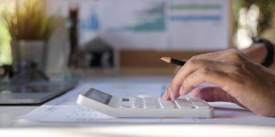 Nahaufnahme eines Geschäftsmannes, der Rechnung unter Verwendung des Rechners am Arbeitsplatz berechnet foto