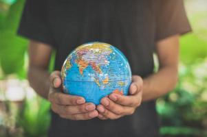 Weltumwelttag .liebe die Welt .hand, die einen Globus hält foto