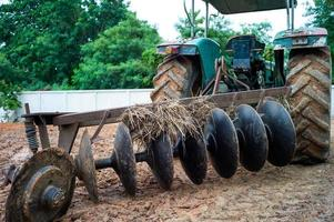 Nahaufnahme von Scheibeneggen auf der Rückseite eines Traktors. schmutzige Stahlschaufeln eines Traktors mit getrocknetem Stroh und Erde foto