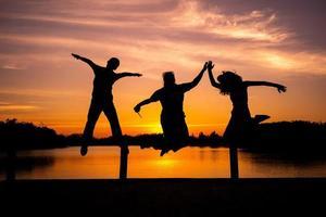 Schattenbildporträtgruppe von Leuten, die mit dem Licht des Sonnenuntergangs im Hintergrund springen foto