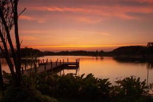 Holzweg in den See mit natürlicher Landschaft des Sonnenuntergangs und der Silhouette des Waldes im Hintergrund foto