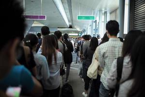 Rückenporträt Menschenmenge, die am Bahnsteig des Bahnhofs auf den Zug wartet foto