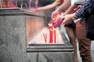 Nahaufnahme Hände halten das Bündel von Weihrauch zum Anzünden mit Kerzen in der Sandschale foto
