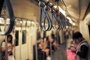 Selektiver Fokus auf eine Gruppe von Handläufen im Zug mit verschwommenen Passagieren und Bokeh-Lichtern im Hintergrund foto