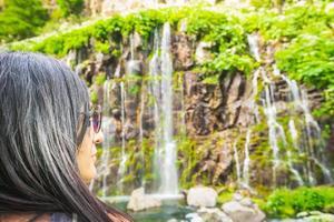 Frau, die einen Wasserfall betrachtet foto