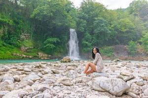 Frau sitzt vor einem Wasserfall foto