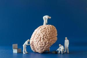 Miniaturmenschen, Wissenschaftler, die das Konzept des menschlichen Gehirns, der medizinischen Gesundheitsversorgung und des chirurgischen Arztes beobachten und diskutieren. foto