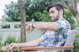 Geschäftsmann schaut auf sein Handgelenk, während er auf einem Ferienrasen sitzt foto