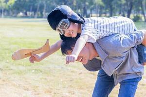 Vater und Sohn spielen Papierflieger im Park. Der Sohn ist auf dem Rücken seines Vaters. foto
