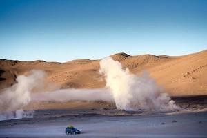 Boivianische Wüstenlandschaft mit Sonnenschein und riesigen dampfenden Geysiren foto