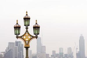 Straßenlaternen auf Westminster Bridge, verschmutzte Wolkenkratzer auf Hintergrund, London, Großbritannien foto
