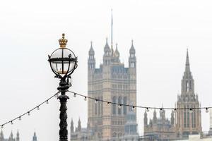 Delphinlampenstandard auf Themse-Böschung in London an der Westminster-Brücke, verschmutzte Westminster-Abtei auf Hintergrund foto
