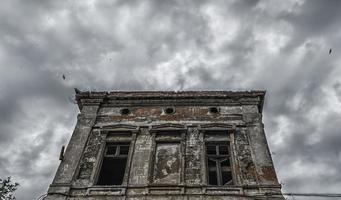 zerstörtes altes Gebäude auf einem düsteren Himmel mit Vögeln foto