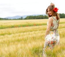 Frau, die in einem Blumenkleid in einem Feld aufwirft foto