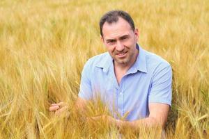 Mann in einem blauen Hemd in einem Roggenfeld foto