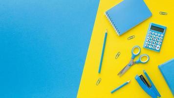 Schere und Hefter mit gelbem und blauem Kopierraumhintergrund foto