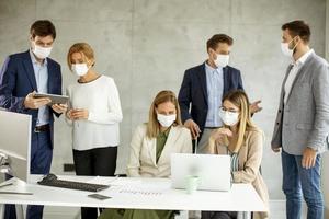 Gruppe maskierter Fachleute in einer Besprechung foto