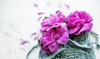rosa Pfingstrosenblumen im Stringbeutel foto