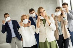 Gruppe von Fachleuten, die Masken aufsetzen foto