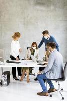 vertikale Ansicht einer Gruppe in einer Besprechung, die Masken trägt foto