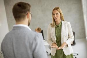 Geschäftsleute, die in einem Büro sprechen foto