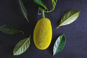 Jackfrucht und Blätter, Jackfrucht auf einem schwarzen Hintergrund foto