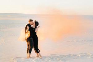 Mann und ein Mädchen in schwarzer Kleidung umarmen sich und rennen mit orangefarbenem Rauch auf dem weißen Sand foto